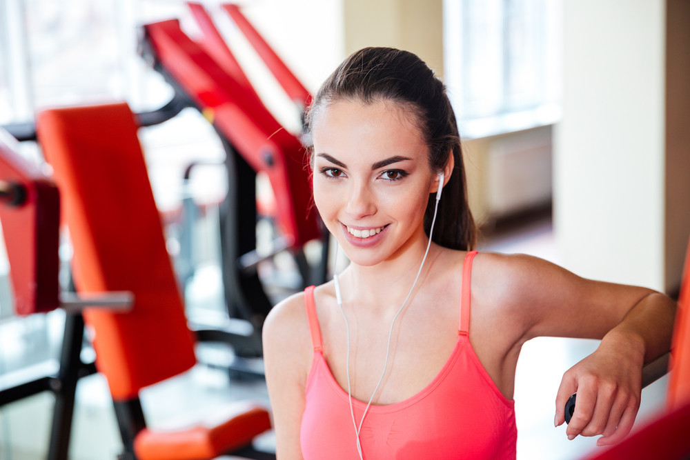 Portrait of beautiful happy young sportswoman in earphones listening to music in gym