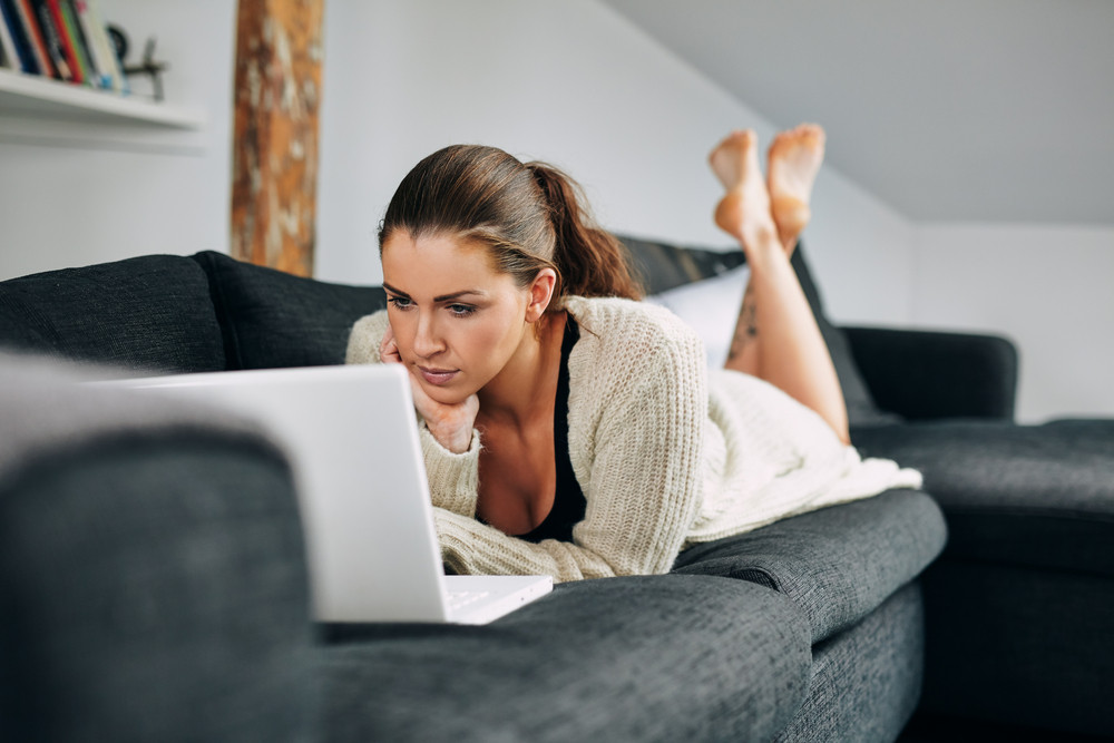 Portrait of beautiful young woman working on laptop while lying on sofa. Female using laptop at home.