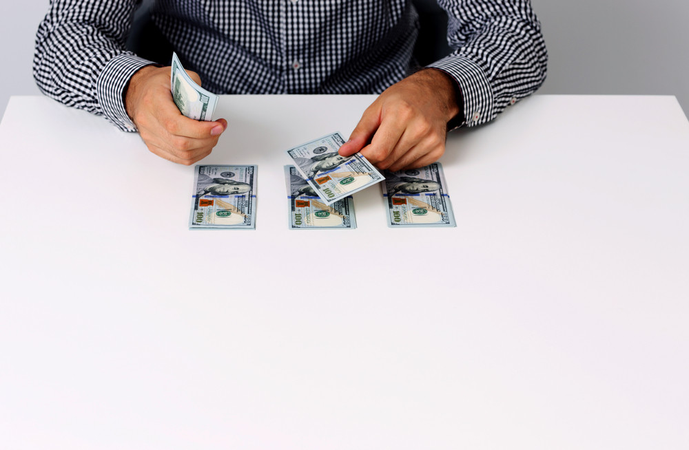 Portrait of businessman counting hundred dollar bills at desk