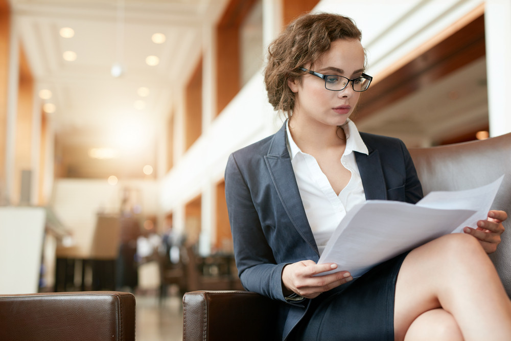 Portrait of businesswoman reading document. Female professional in hotel lobby examining papers.