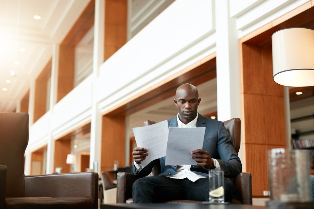 Portrait of busy young businessman sitting at hotel lobby going through documents. African business executive reading contract papers.