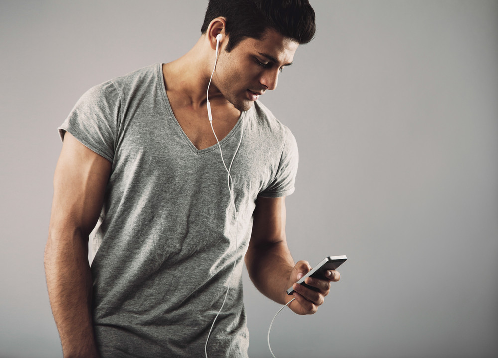 Portrait of casual young man with cell phone and headphones listening to music on grey background. Enjoying listening music on smartphone.