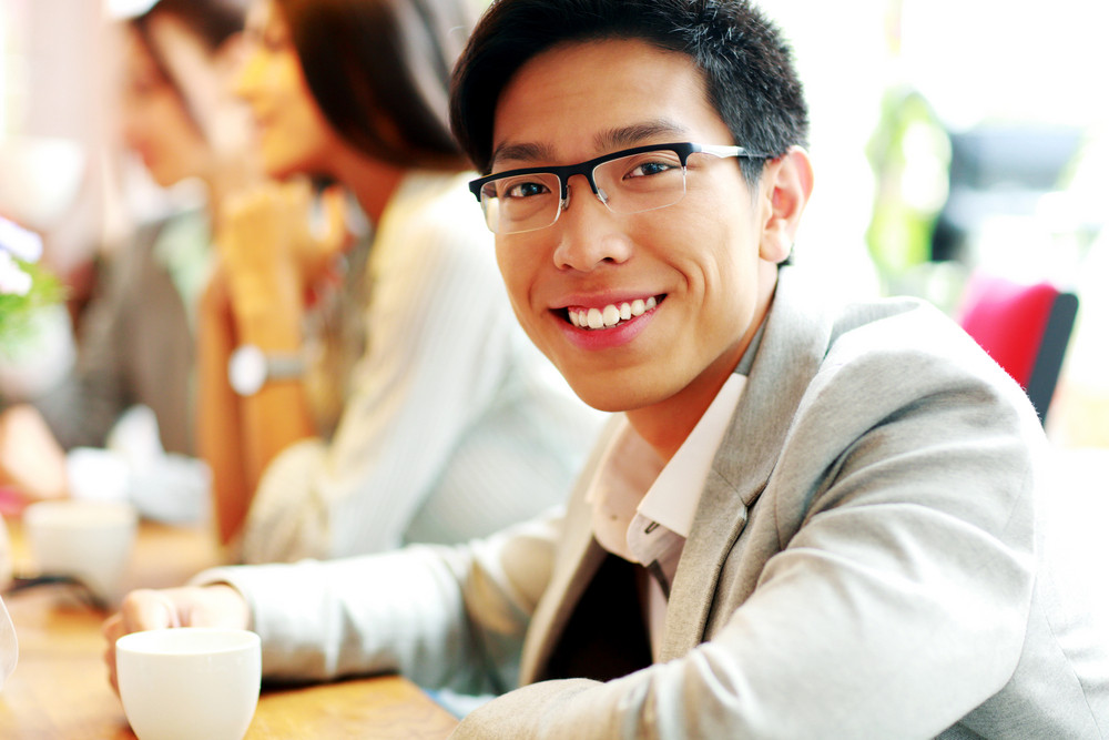 Portrait of cheerful businessman sitting in front of colleagues