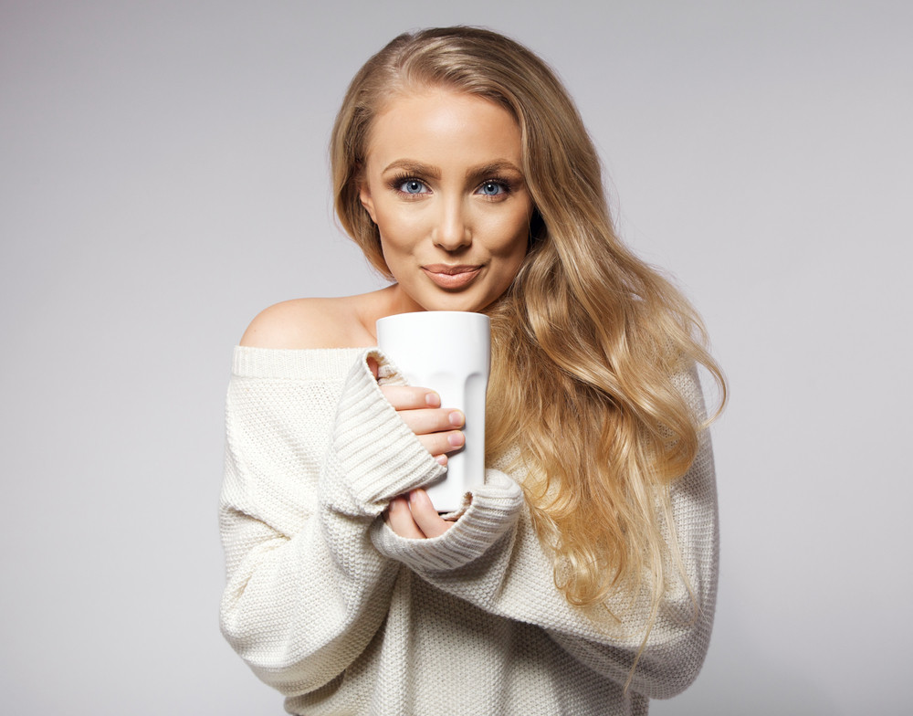Portrait of cute young woman wearing sweater drinking coffee. Beautiful caucasian female model with cup of hot coffee on grey background.