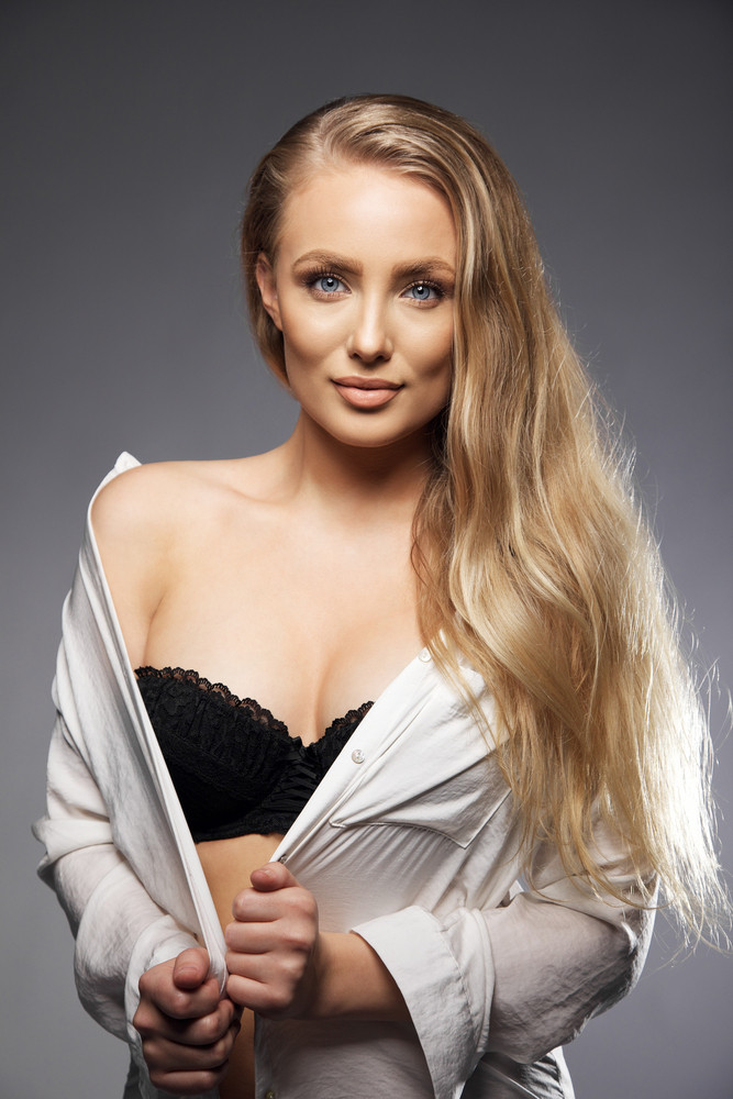 Portrait of elegant young woman wearing black lingerie. Sexy blonde on grey background. Sensuous caucasian female model with long hair.