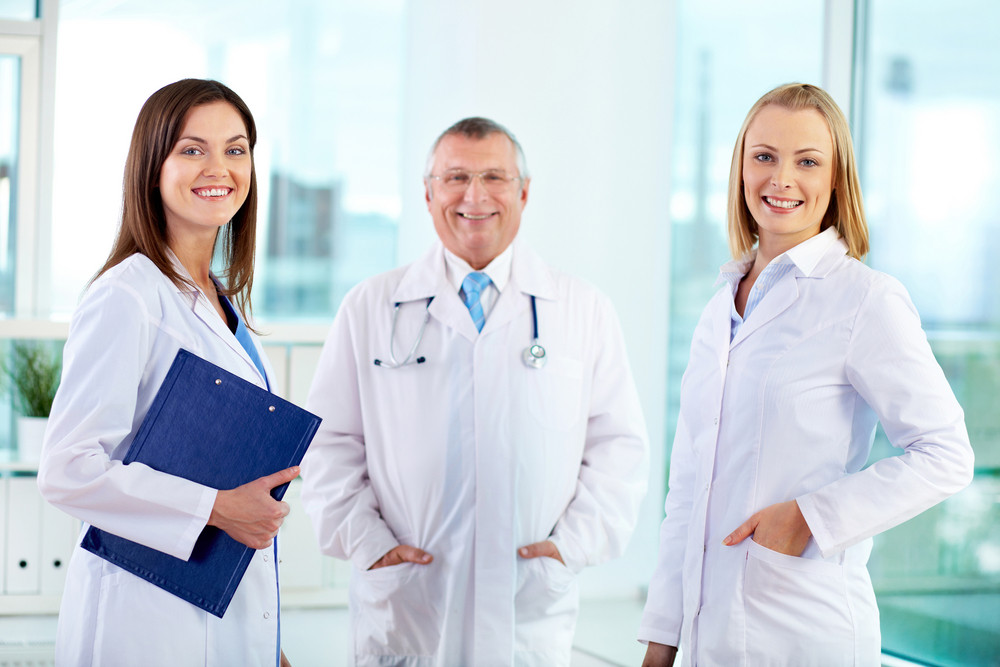 Portrait of female clinicians looking at camera with senior doctor on background