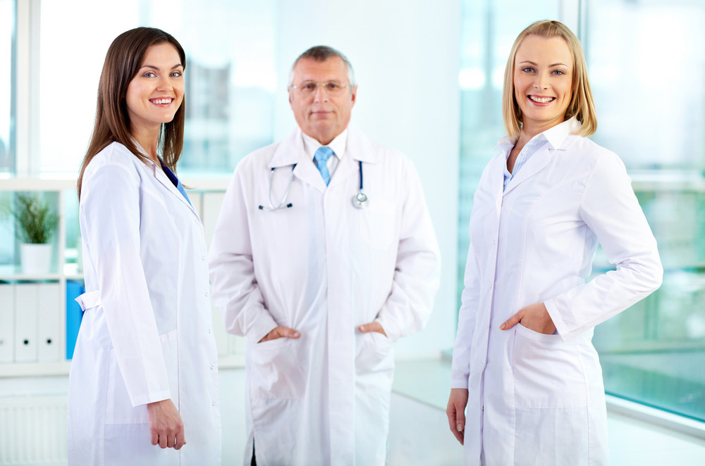 Portrait of happy nurses looking at camera with mature doctor behind