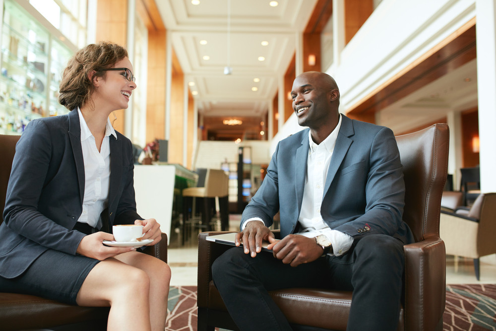 Portrait of happy young businesswoman in meeting with business partner at hotel lobby. Business people having a casual talk during meeting.