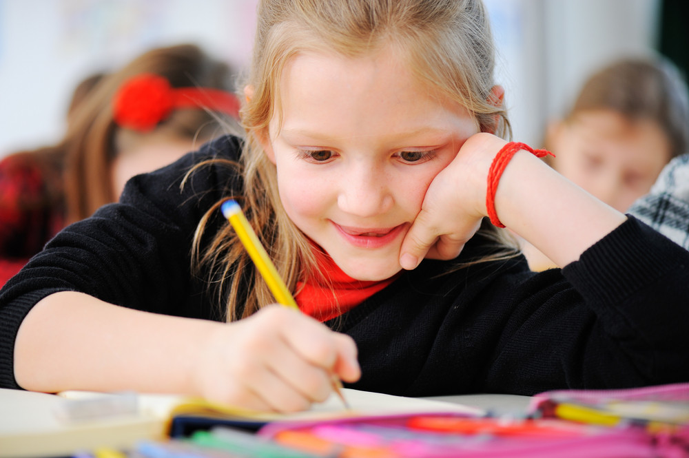 Portrait of happy young girls writing notes with friends in background