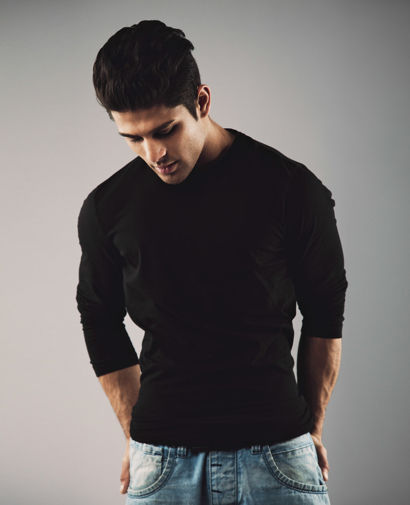 Portrait of hispanic young man standing on grey background looking down thinking.