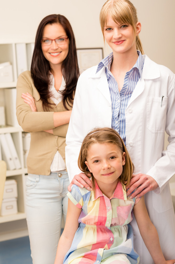 Portrait of little girl with pediatrician and mother in background
