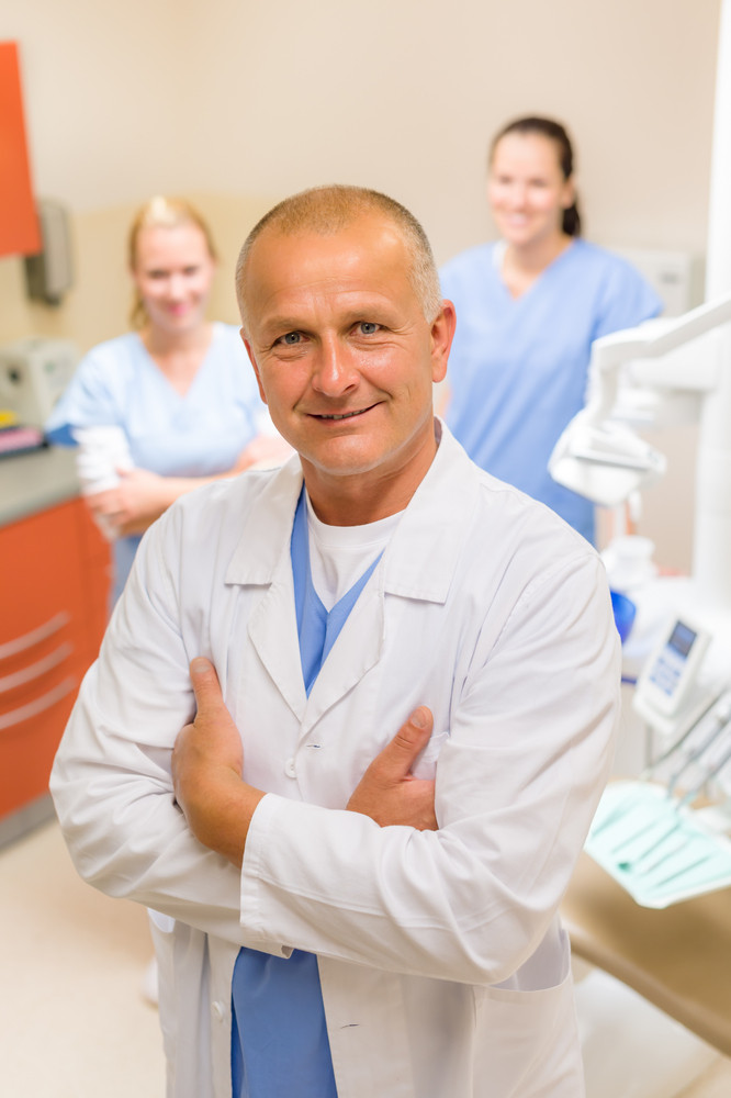 Portrait of mature dentist man with team in stomatology clinic