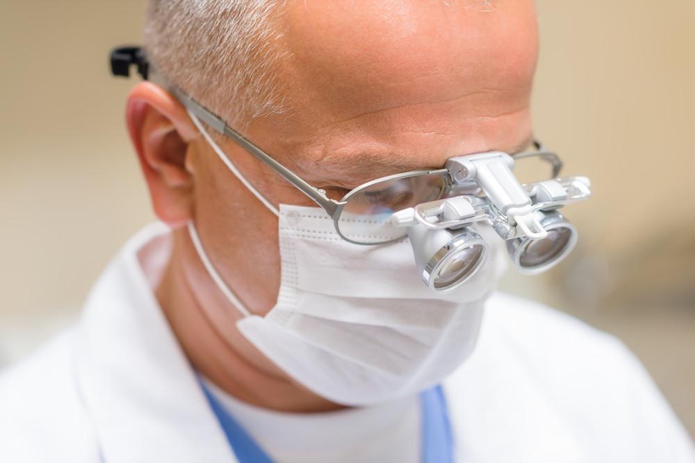 Portrait of mature dentist surgeon wear special glasses technology equipment