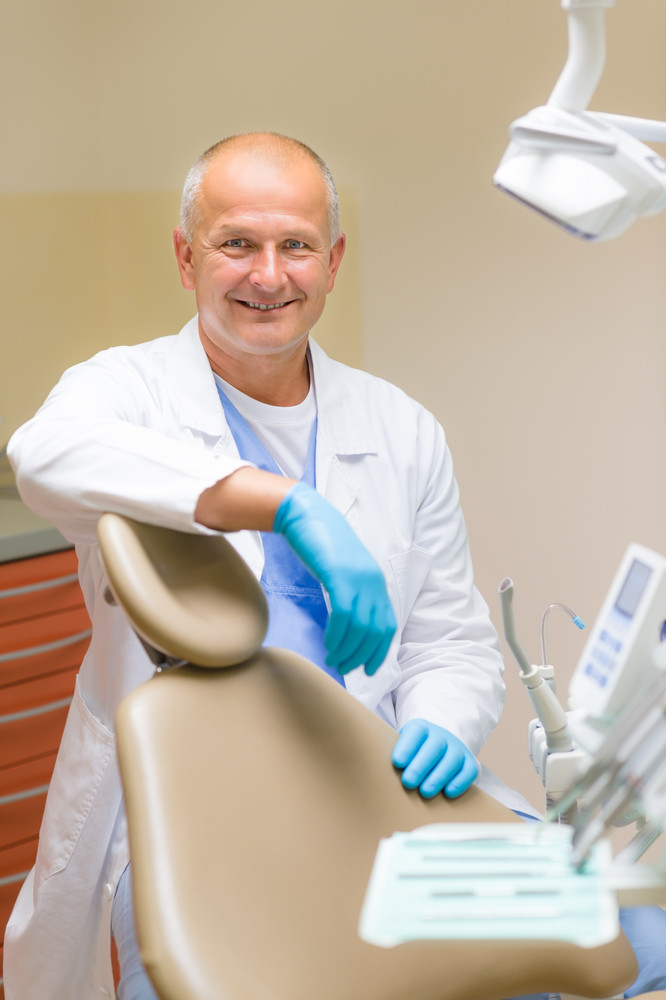 Portrait of mature smiling dentist sitting in modern dental surgery