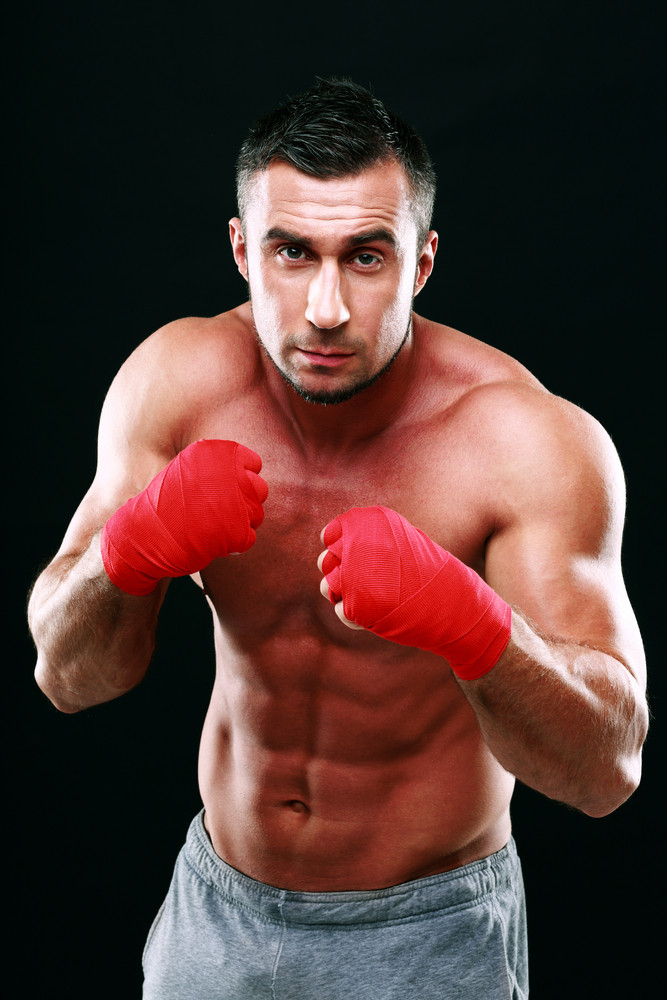 Portrait of muscular male boxer in stance over black background