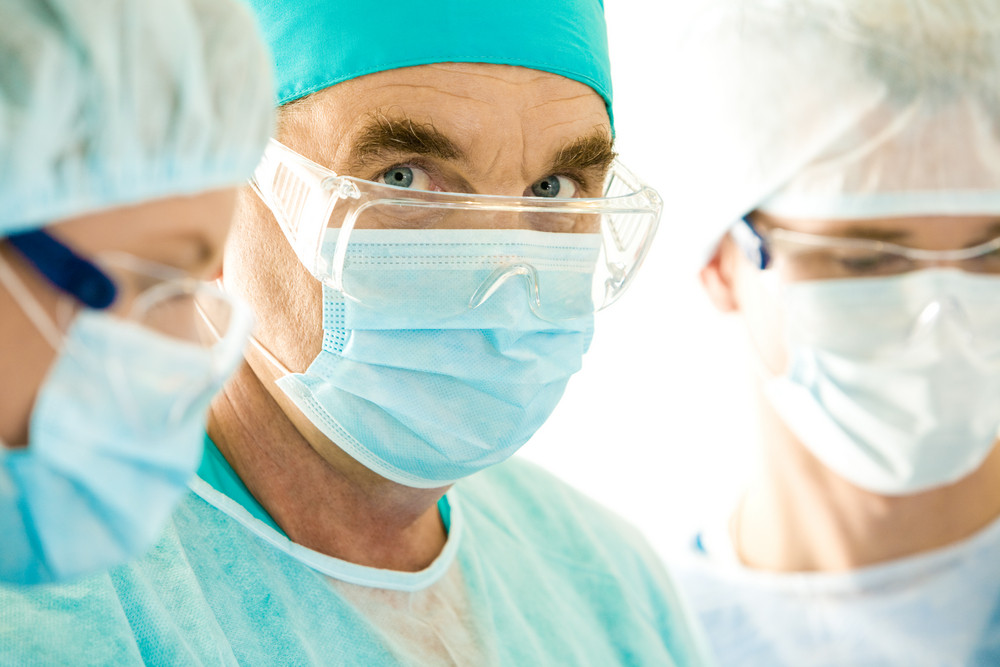Portrait of senior doctor looking at camera through eyeglasses