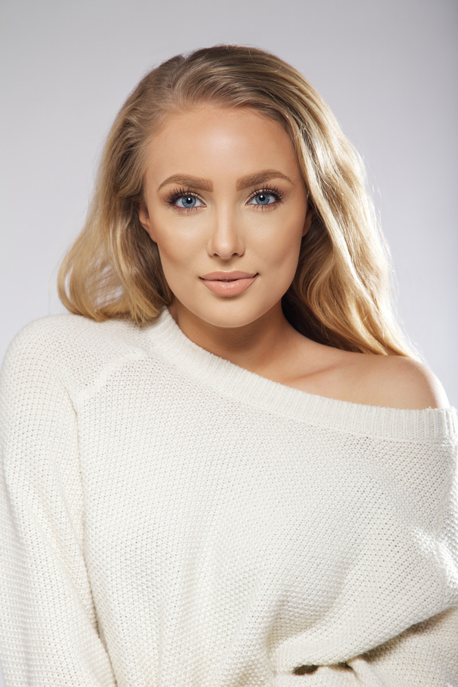Portrait of sensual young female model wearing white sweater looking at camera. Blond woman on grey background.