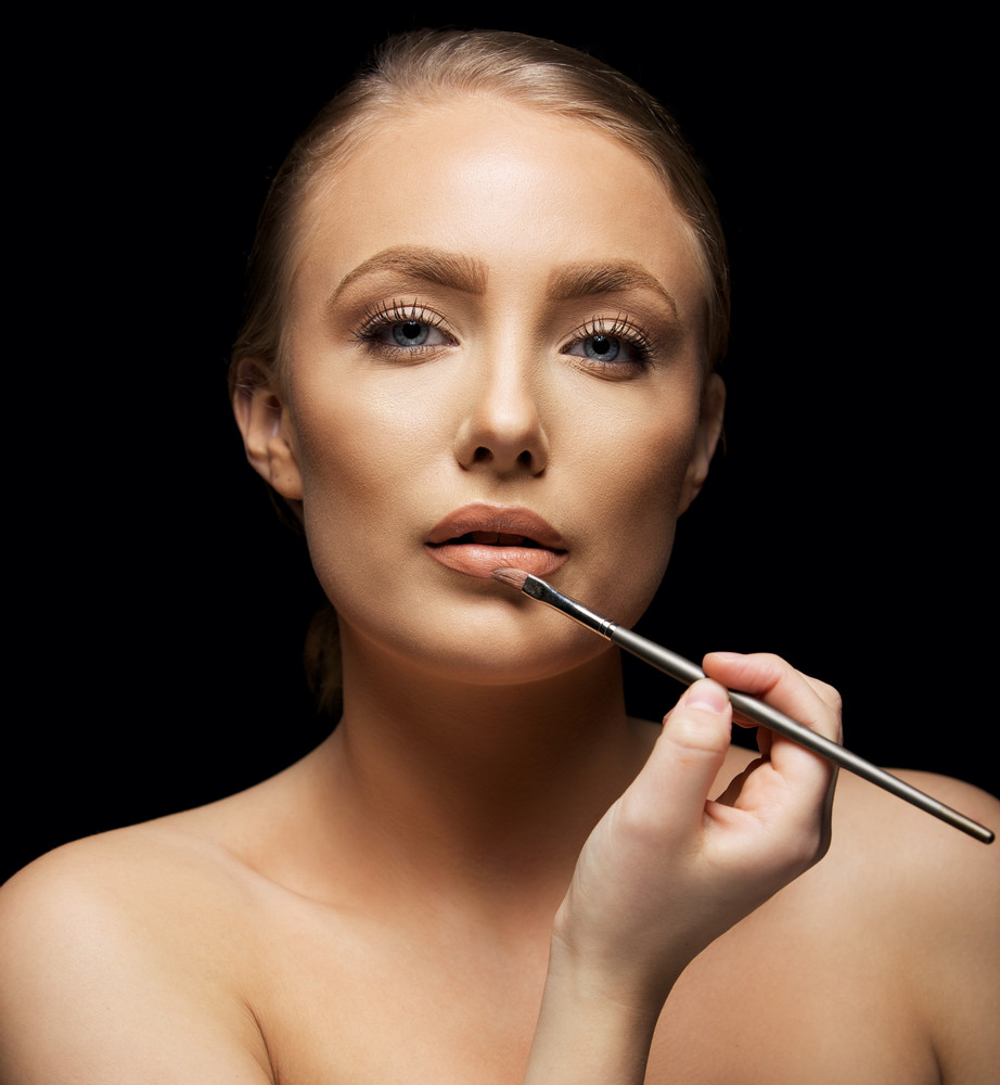 Portrait of shirtless young woman applying lipstick with a brush. Beautiful caucasian female fashion model against black background.