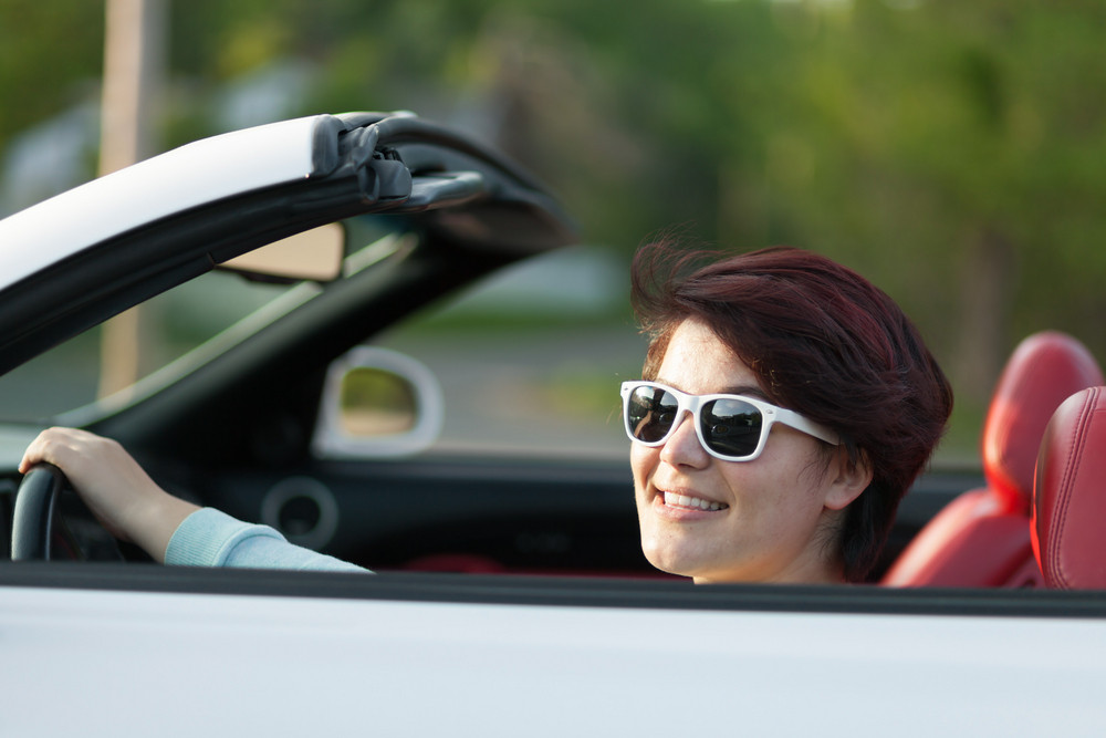Portrait of smiling woman driving a convertible sports car with red leather interior. Shallow depth of field.