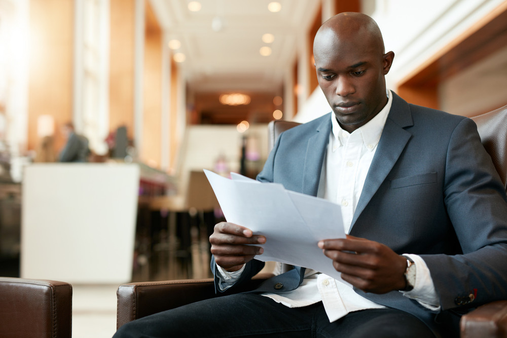 Portrait of young african businessman sitting at hotel lobby reading documents. Business executive going through paperwork.