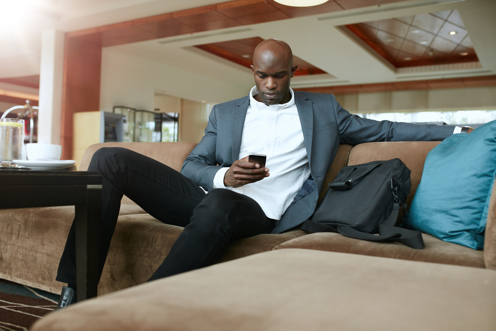 Portrait of young businessman sitting on couch reading text message on hi mobile phone. African business executive waiting in hotel lobby.
