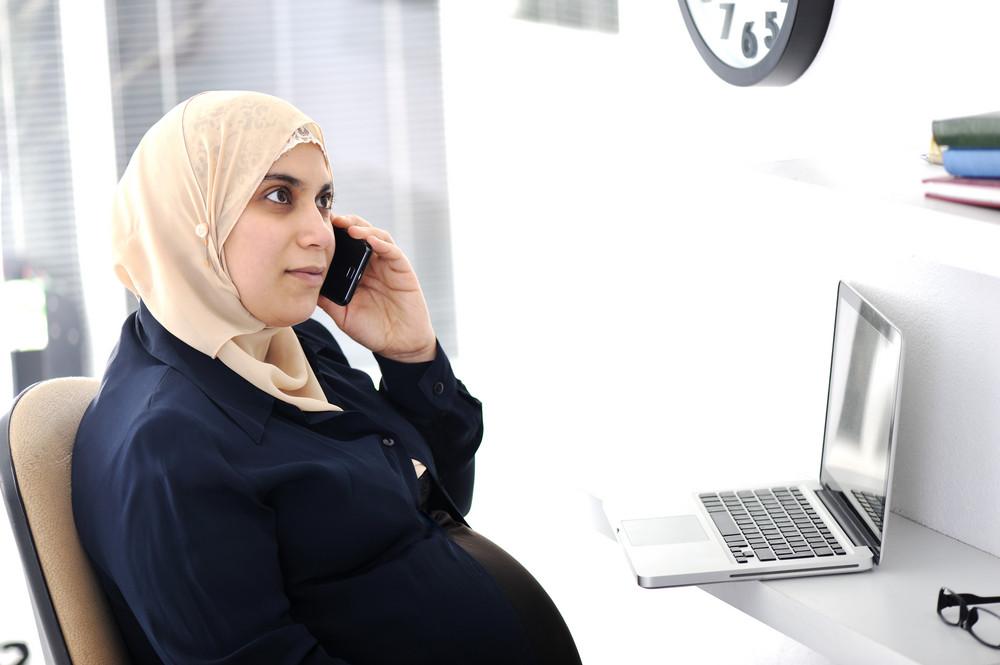 mulher de negócios árabe muçulmano grávida que trabalha no escritório