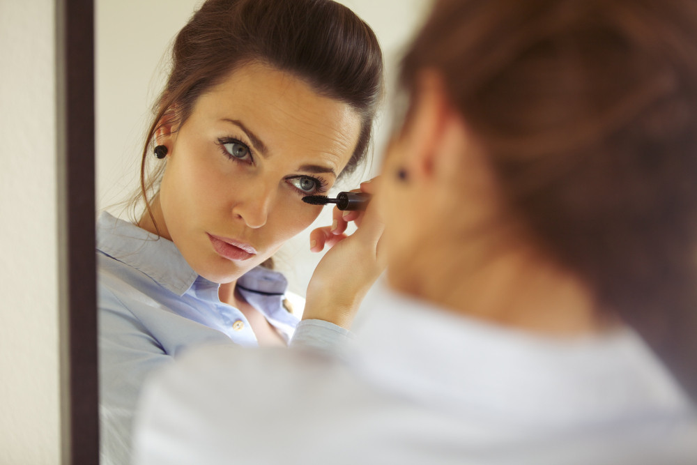 Pretty female looking in mirror and putting on mascara, Businesswoman applying makeup. Caucasian female model getting ready.