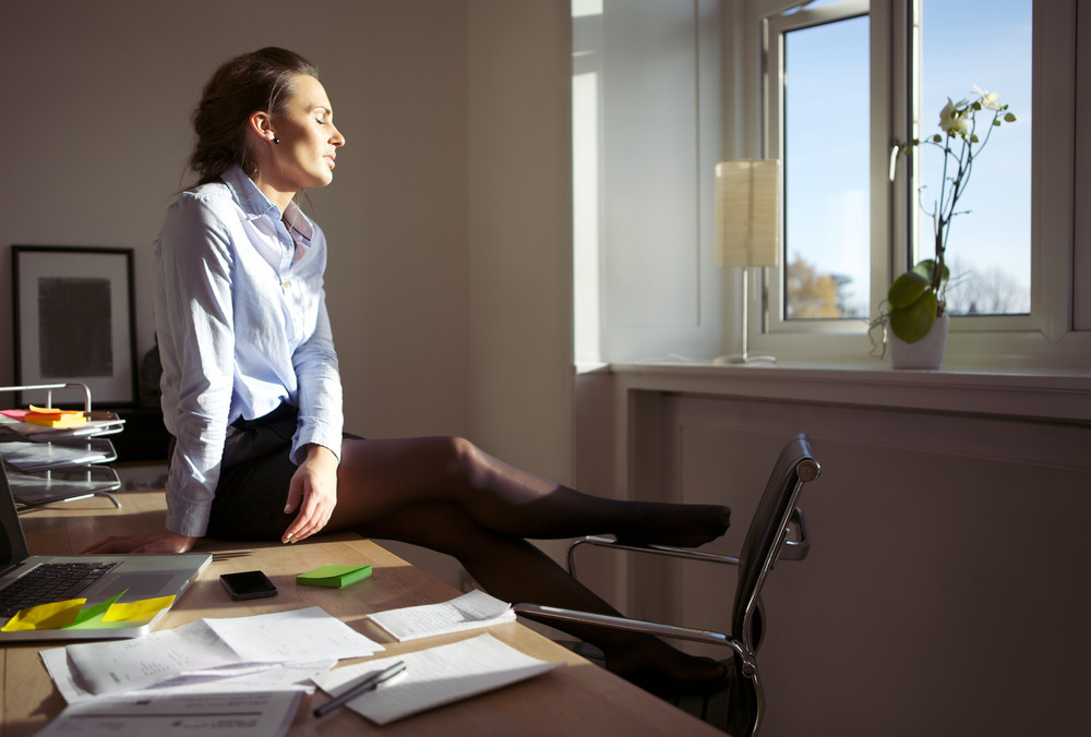 Pretty woman enjoying the sun. Businesswoman sitting on desk with her eyes closed relaxing in sunlight. Caucasian female model in office.