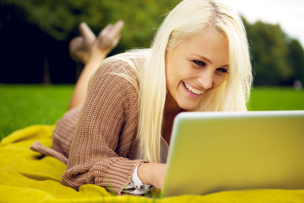 Pretty woman with laptop laughing