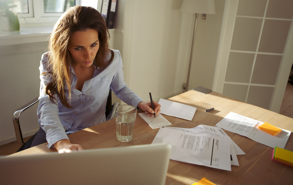 Pretty young businesswoman sitting at desk writing notes from a laptop at home. Beautiful caucasian woman working from home office.