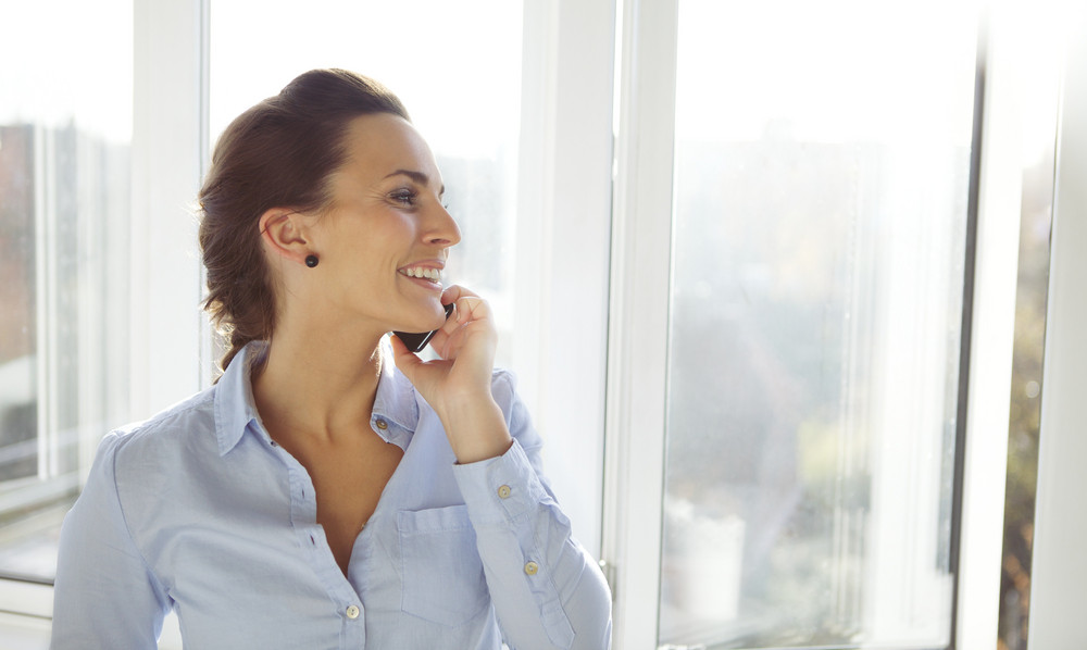Pretty young female business executive talking on mobile phone while standing by window and looking outside. Caucasian businesswoman in office using phone.