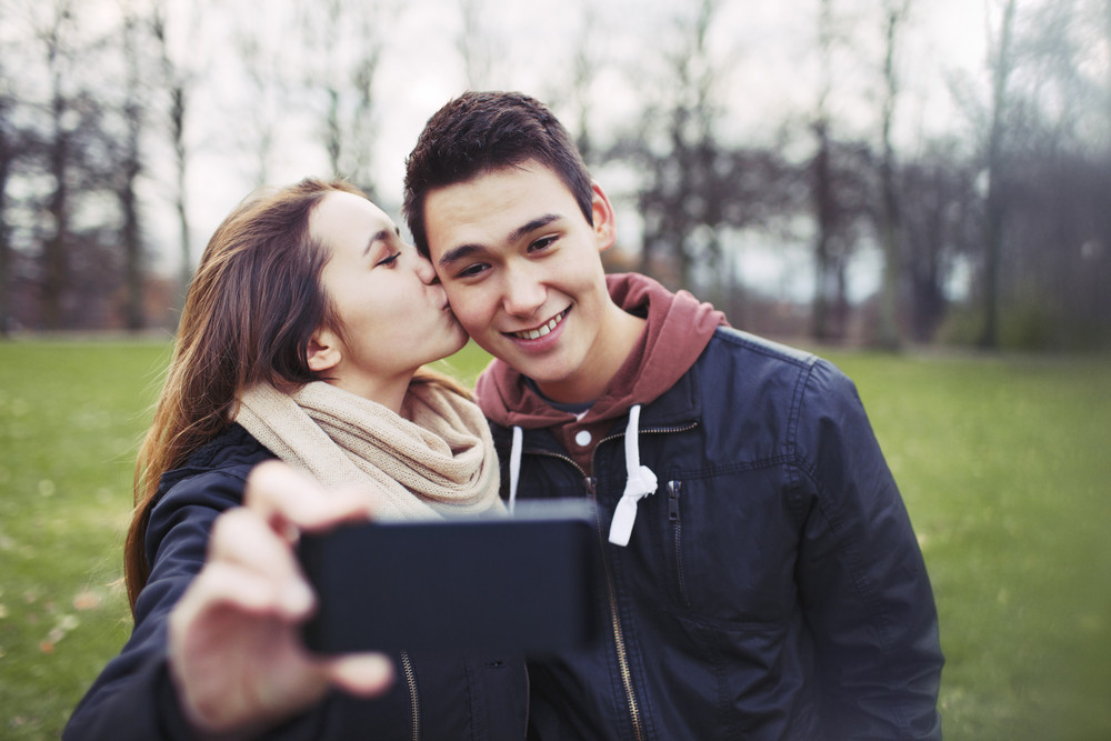 Pretty young girl kissing her boyfriend on cheeks while taking self portrait with a mobile phone. Mixed race couple in park.
