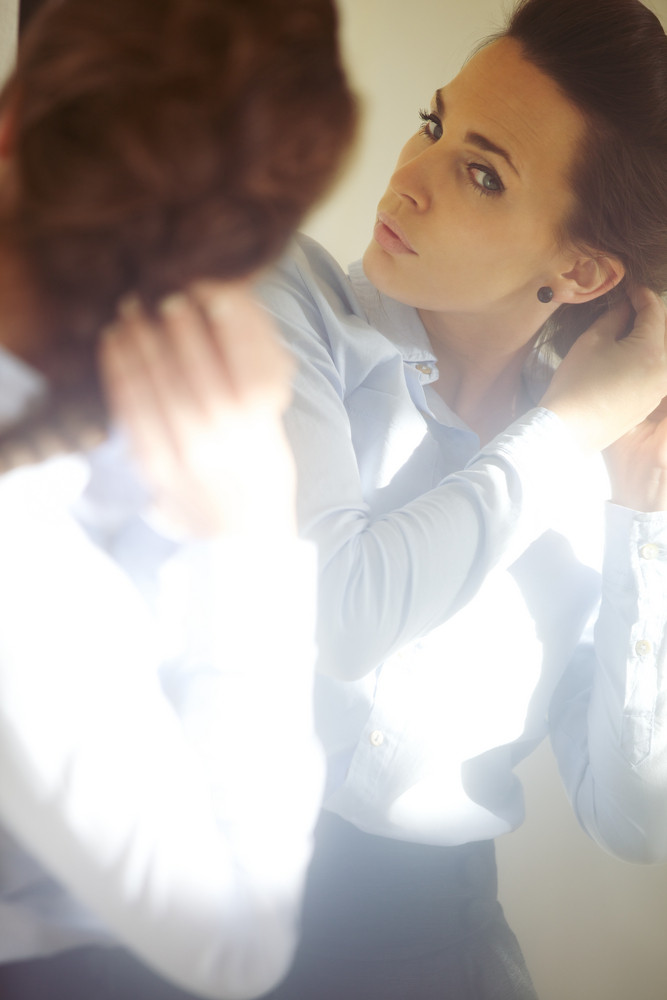 Pretty young woman fixing her hair in front of mirror. Businesswoman getting ready for work. Caucasian female model.