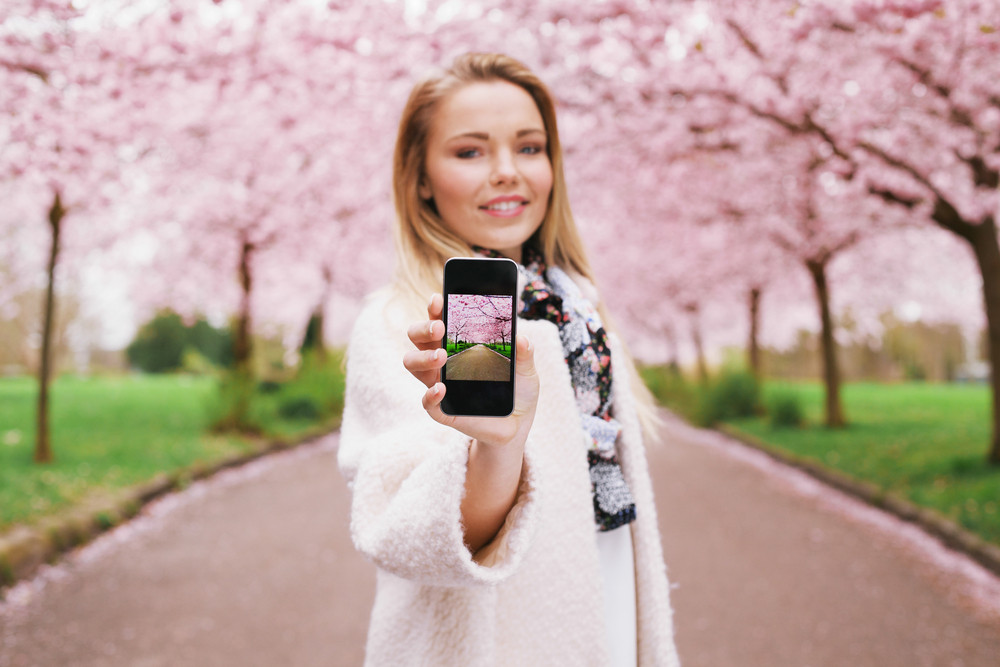 Pretty young woman showing picture of spring blossom garden while standing at a park. Caucasian young female showing spring park picture on her mobile phone.