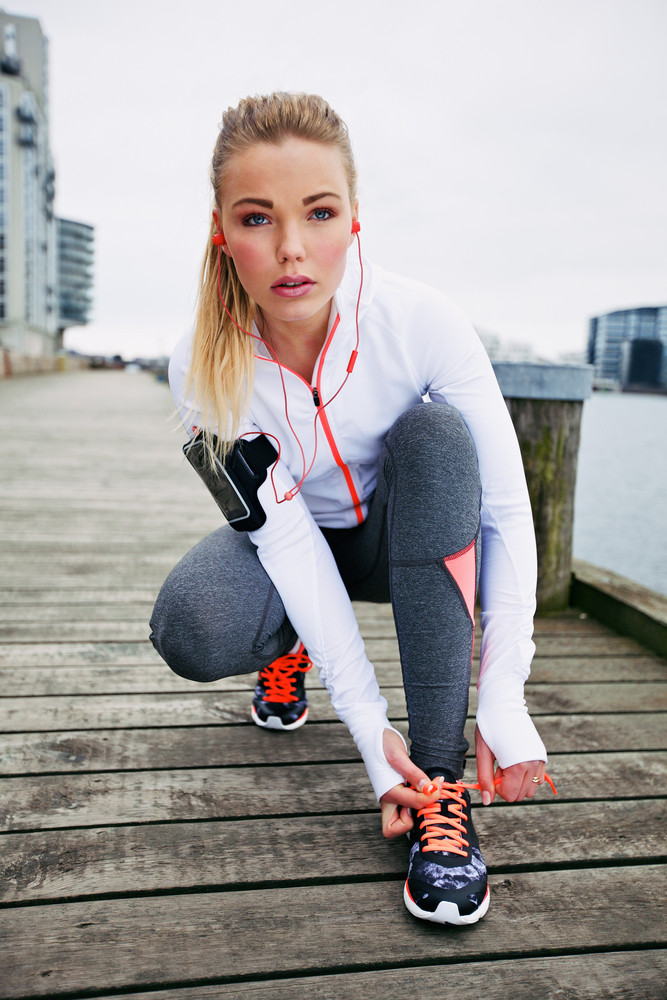 Pretty young woman tying her shoe laces before a run. Fit young female runner training outdoors.