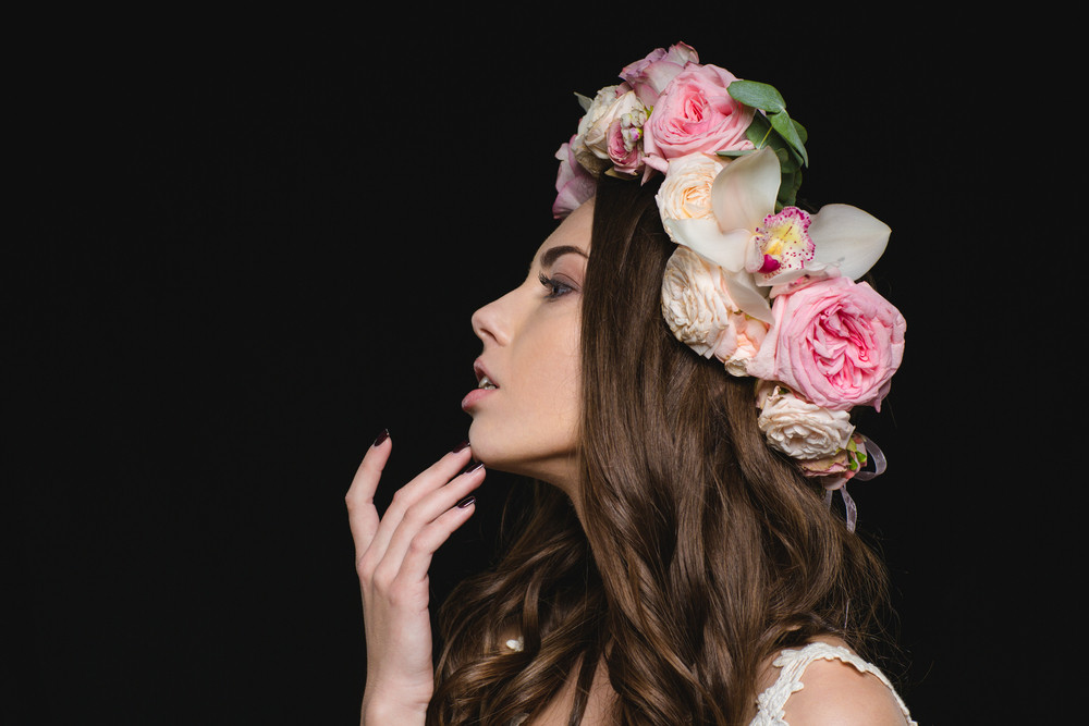 Profile of sensual young woman with long curly hair in flower wreath over black background