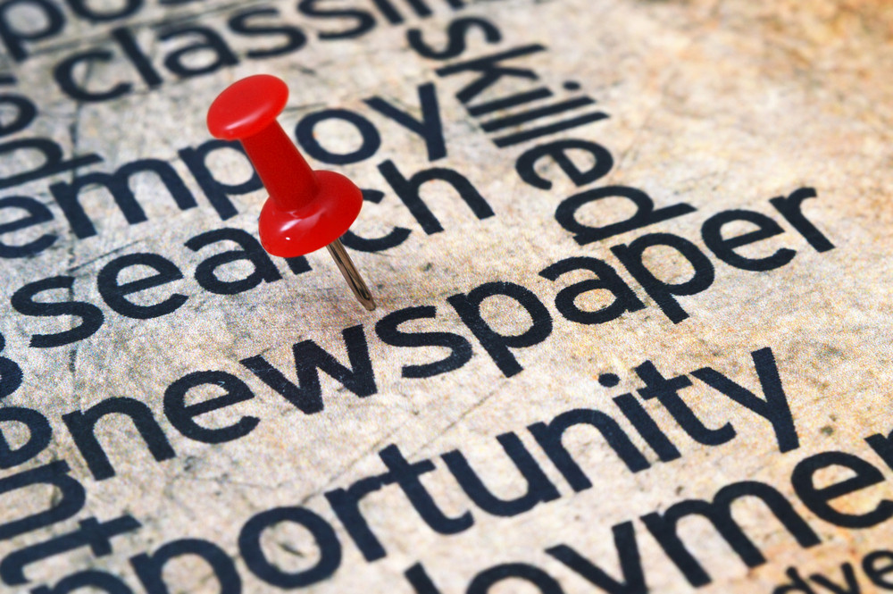 Pushpin On Newspaper Text
