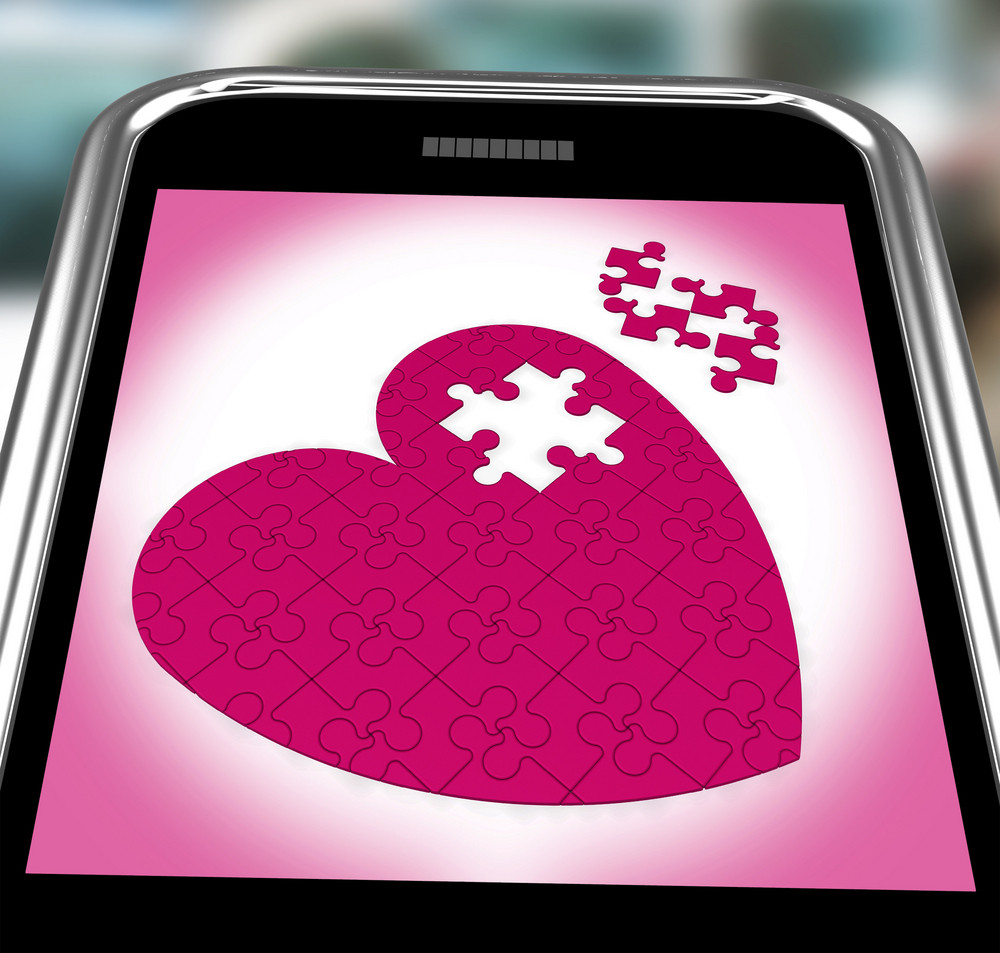Puzzle Heart On Smartphone Showing Commitment