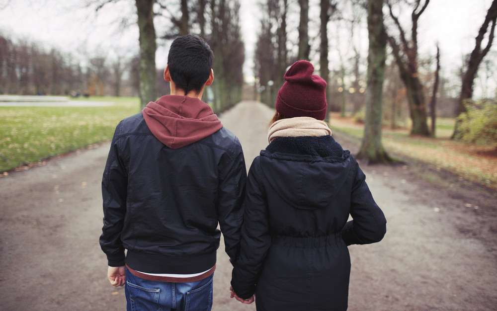Rear view of teenage couple walking in park holding hands. Young man and woman in warm clothes outdoors.