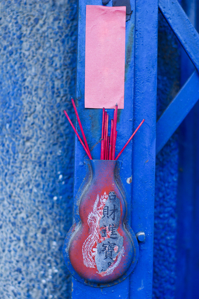 Red chinese incense put on blue door front of house
