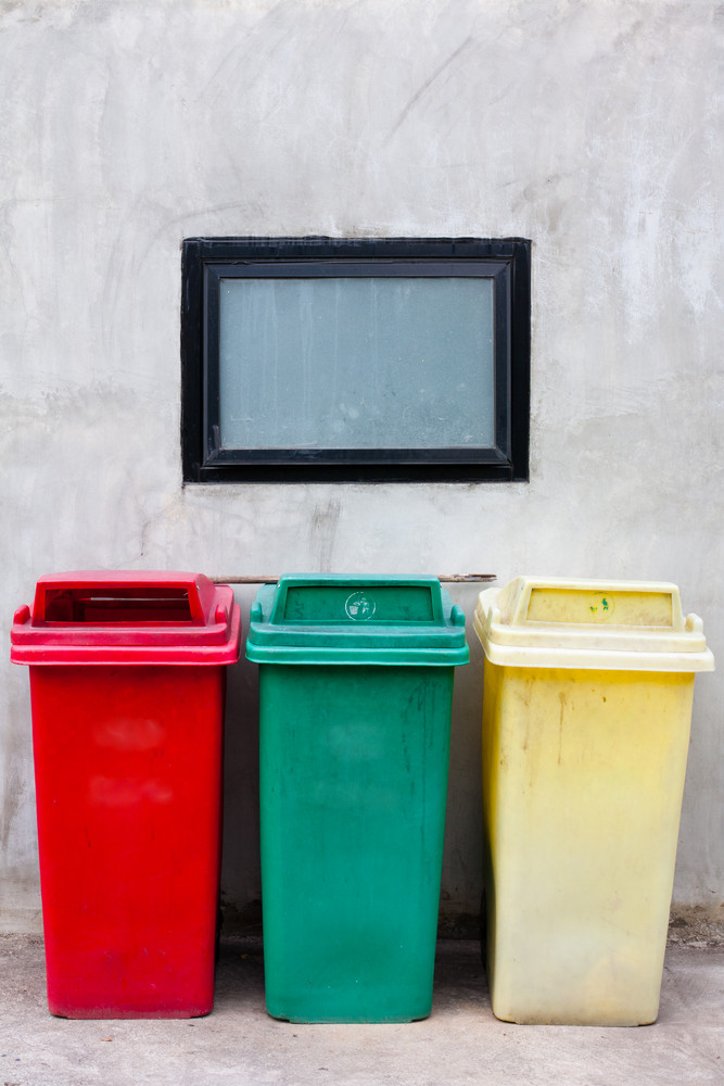Red green and yellow recycle bin on wall
