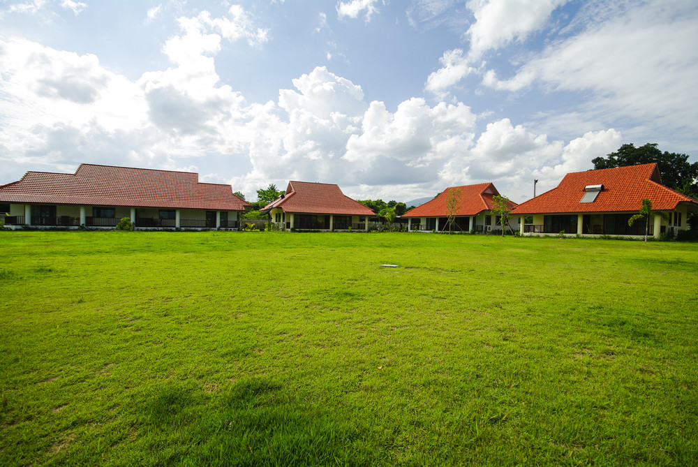 Red painted barns behind a green field of grass in the Thailand countryside.