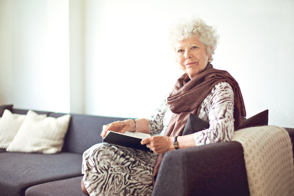 Relaxed grandmother sitting on the couch at home