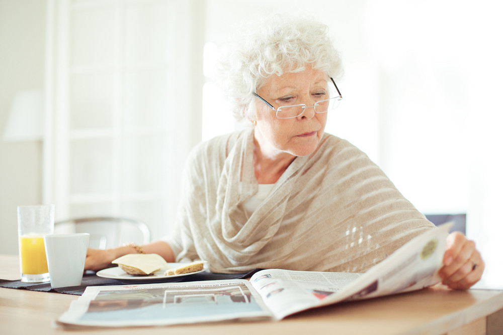 Relaxed senior woman having her breakfast and reading the morning news