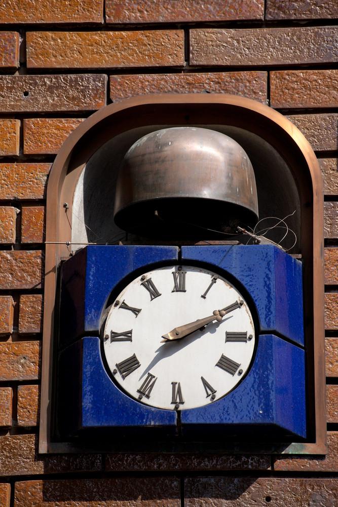 Retro clock hanging on brick wall