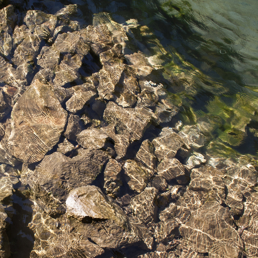 Ripples creating shadows on to stone in water