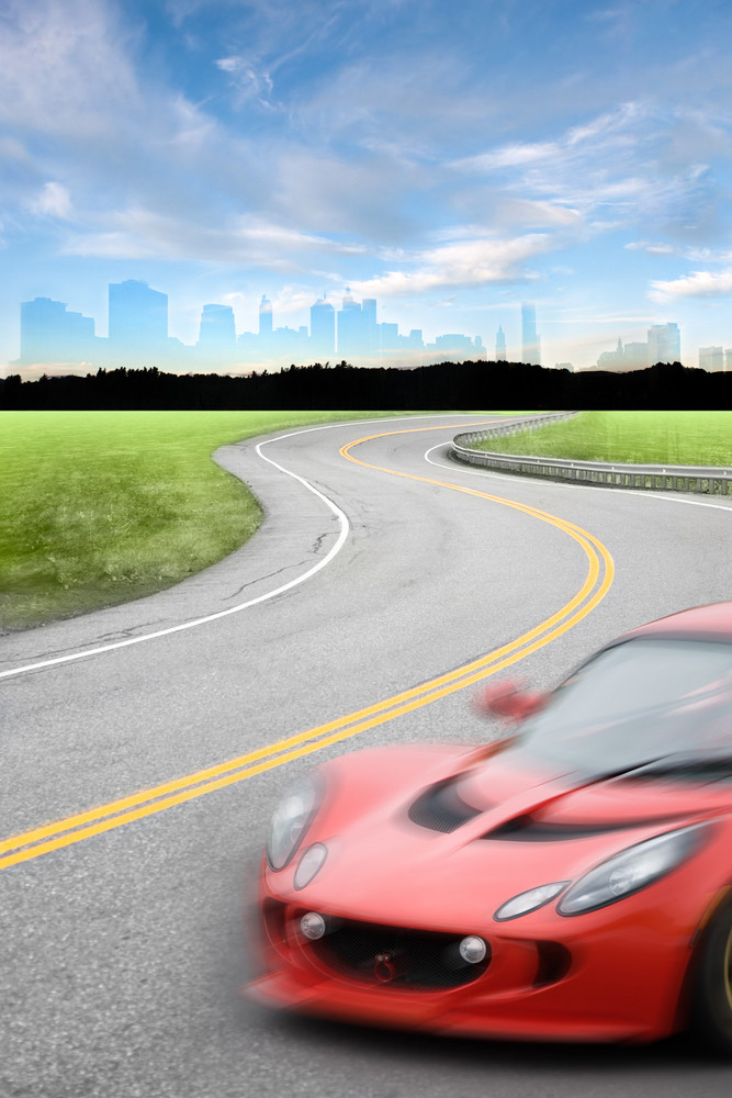 Road scene with a speeding car with motion blur driving down a winding road away from the city skyline.