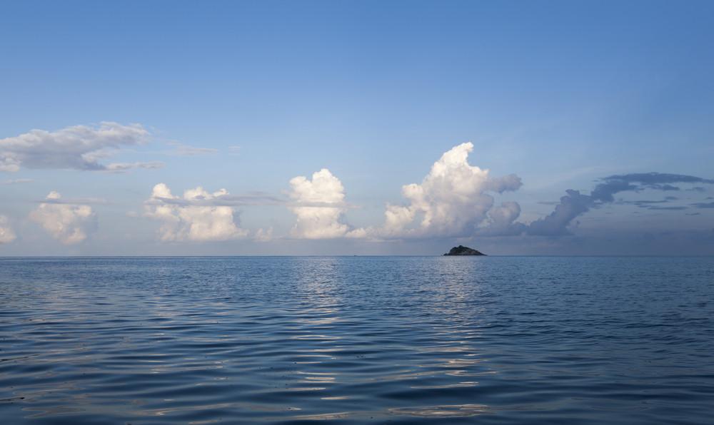 Rock in the ocean under a blue sky