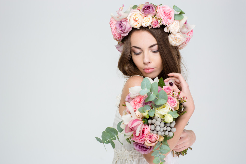 Romantic cute lovely young woman in beautiful wreath of roses posing with bouquet of flowers