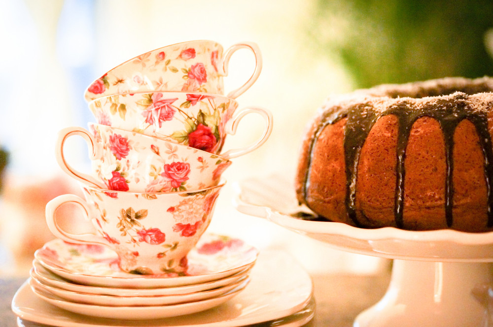 Round Cake With Chocolate Glaze On White Stand With Tea Cups In Roses